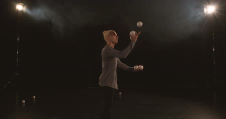 entertainers : Juggler in the black studio makes tricks with five balls Stock Footage