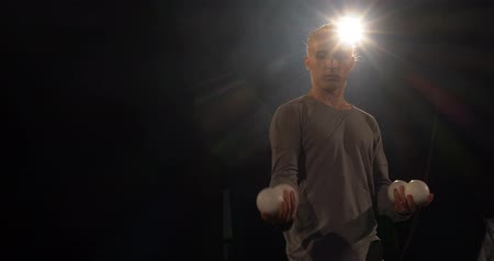 entertainers : Juggler in the black studio and four balls in his hands. Stock Footage