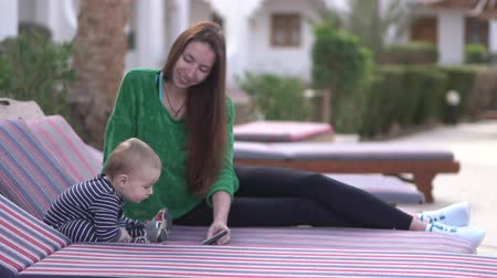 мультфильмы : Mom and baby are enthusiastically watching videos on a smartphone on a lounger Стоковые видеозаписи