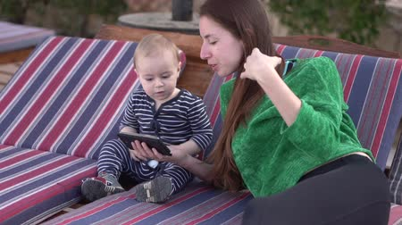socializing : Mom shows video on the phone to the baby and teaches him to dance in slow motion Stock Footage