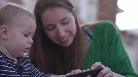 socializing : Chubby serious babe clicks smartphone sitting near mom in slow motion close up Stock Footage
