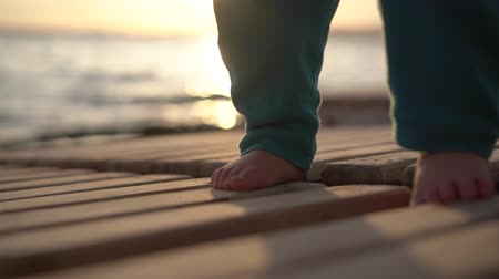 baby chubby : Legs of a small child are slapping on a lounger near the sea in slow motion. Stock Footage