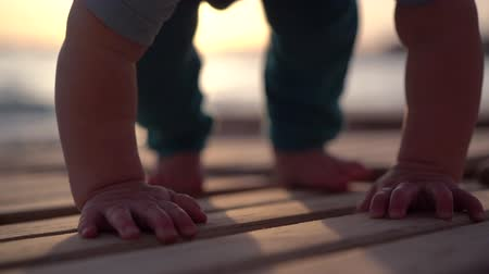 家庭 : Small beautiful baby boy crawling on a wooden lounger near the sea during sunset