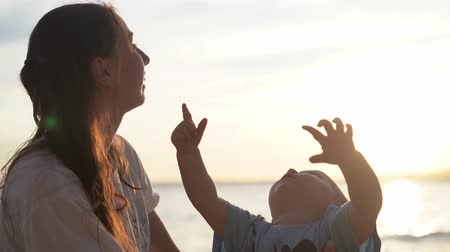lelkesedés : Mom and little child watch with enthusiasm and show the flying bird in the sky.