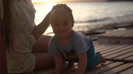 caresses : Girl strokes the head of a little baby on the evening beach in slow motion