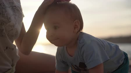 caresses : Mom strokes a beautiful cheerful baby during sunset in slow motion Stock Footage