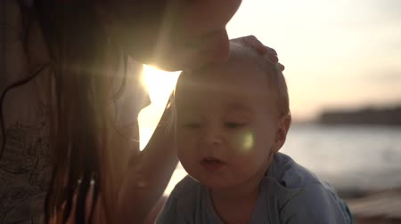 caresses : Mom kisses a beautiful baby in the head sea close up in slow motion