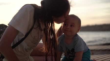 caresses : The mom kisses a cute baby at sunset in slow motion Stock Footage