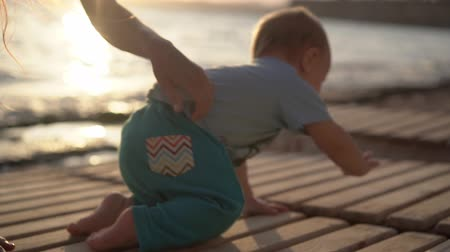 emeklemek : The mom tickles a little baby near the sea at sunset in slow motion