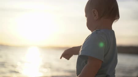 point of interest : A baby shows interest at something near the sea by his finger in slow motion
