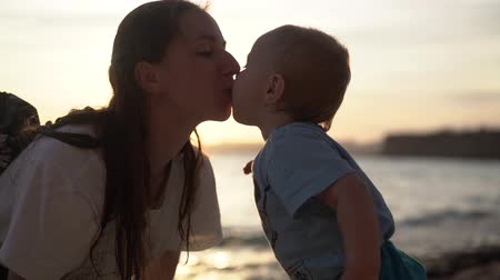caresses : Mom kisses a little baby and he reaches out for her at sunset in slow motion Stock Footage