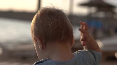 nape : The baby beats his ear by the hand in slow motion Stock Footage