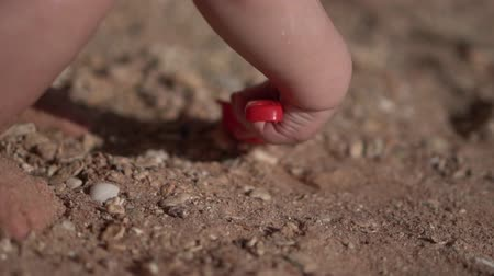 kielnia : The baby digs sand with a shovel close up in slow motion