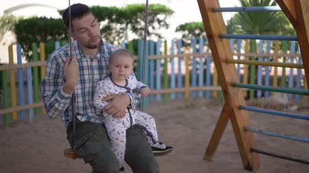 natal : Tired dad closes his eys sits on a swing with a tired baby in slow motion Stock Footage