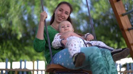 vazba : Young mother and baby ride on a swing in slow motion Dostupné videozáznamy