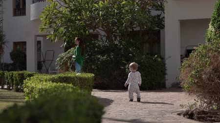 málo : The little baby is walking along the path behind the mother in slow motion.