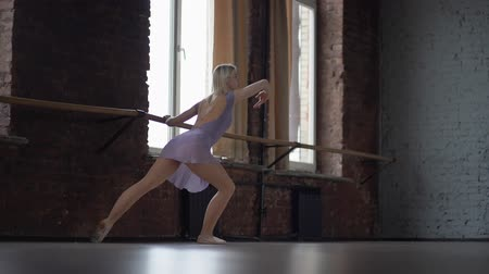 sapma : Ballet class and warm up. Blone girl in the studio in slow motion.