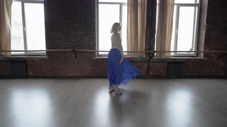 tornász : Amazing slow motion - blonde dancer in blue skirt makes wheel in the studio. Stock mozgókép
