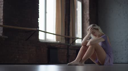 színésznő : Depression and fatigue of a dancer who sits on the floor. Stock mozgókép