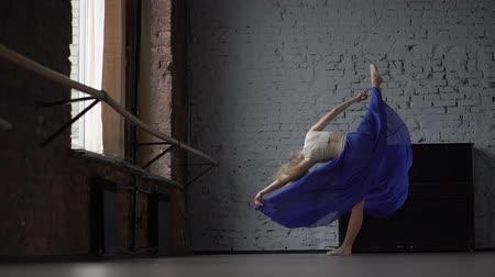 seu : Blonde dancer in blue skirt makes split on one leg in slow motion.