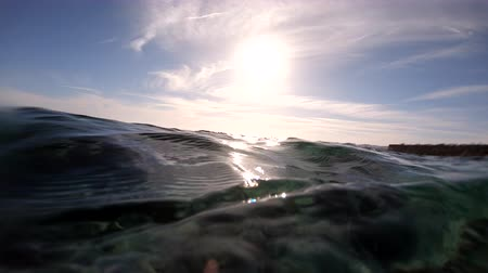 formação rochosa : 4k - beautiful underwater shot with sunlight sunbeams on the surface of water.