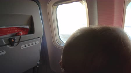 típico : Mother with child sits on the airplane near window during start of flight.