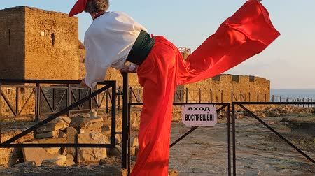 tiltott : Man in Ukrainian suit with stilts climbing over a fence at a fortress in slo-mo