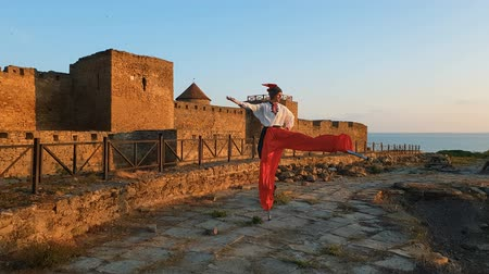 otimismo : Man in a Ukrainian folk costume standing on stilts at a fortress in slo-mo