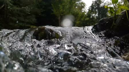 hurry up : Blurred swift streams of water falling among boulders in summer in slo-mo