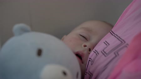 újszülött : 4k - cute little baby sleeps on the hands of his mother during airplane flight.
