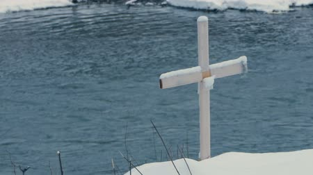 dead wood : Wooden cross standing on a mountain riverbank in Bukovel in winter in slo-mo