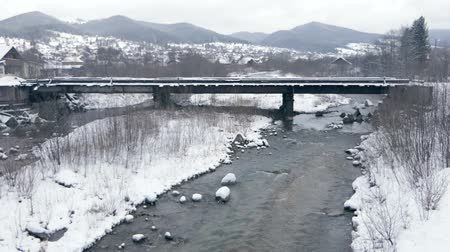 elba : Narrow stream flowing under a bridge in the Carpathians in winter in slo-mo