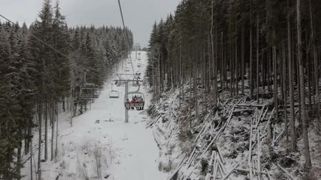 chair lift : Happy tourists moving on a long ski lift in the Carpathians in winter in slo-mo