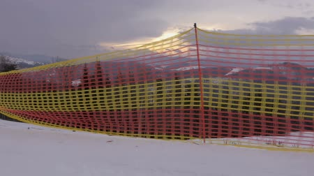 obdélníkový : Red and yellow net limiting a ski route in the Carpathians in slo-mo