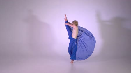 scuola di ballo : Cute blonde girl spinning and doing a vertical leg split in studio Filmati Stock