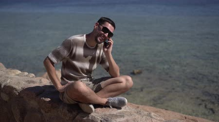 towel white : Man sits on the stone bench on the rocky beach and talk on the phone. Stock Footage