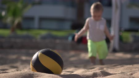 volleyball : 4k - little boy walks near valleyball ball on the beach.