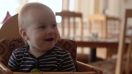 puericultura : 4k -Small baby sits on the baby chair and eats food. Stock Footage