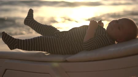 strandlaken : Cute baby rest with bread on his hand at sunset in slow motion.
