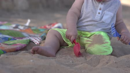 ancinho : Cute little baby plays on the beach with paddle, rake and sand.