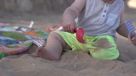 熊手 : Cute little baby plays on the beach with paddle, rake and sand.