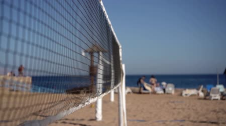залп : Focusing on the volleyball net in slow motion on the beach of the sea.