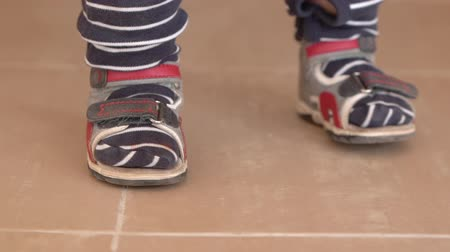 サンダル : Cute little feets of the small kid in slow motion and stripes.