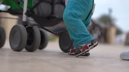 resmedilmeye değer : Slow motion - legs of the little kid and mother near stroller Stok Video