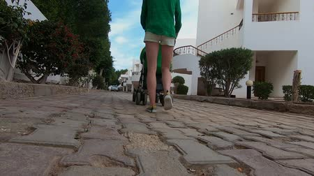 puericultura : Young girl walks with stroller in slow motion. Stock Footage