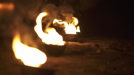 excluir : Bowls with fire shine and burn in slow motion.