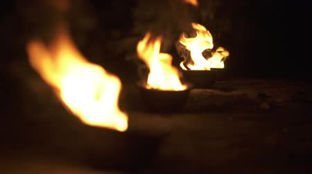 apagar : Bowls with fire shine and burn in slow motion.