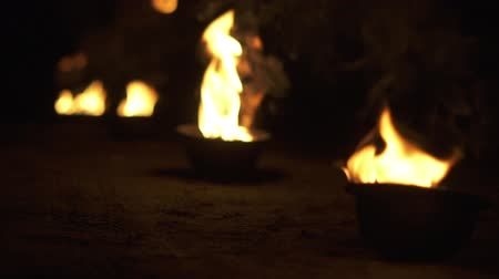 excluir : Focusing on the bowl with fire that shine and burn in slow motion.