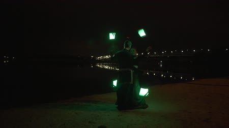 сказка : Two artists make led show on the bank of the river Dnipro in Kyiv at the night.