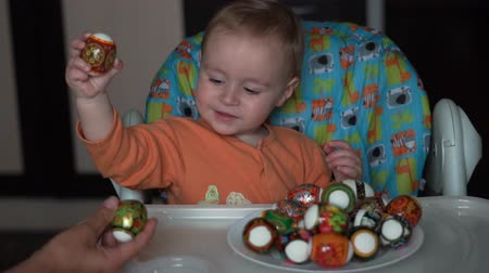 perso : Little baby has fun on the kitchen he fight with easter eggs in slow motion.